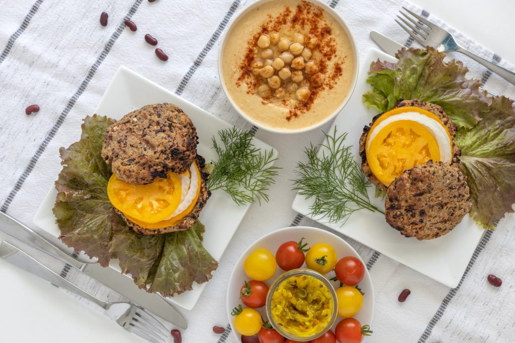 Vegan seitan burgers served as patties with hummus, tomatoes and greens